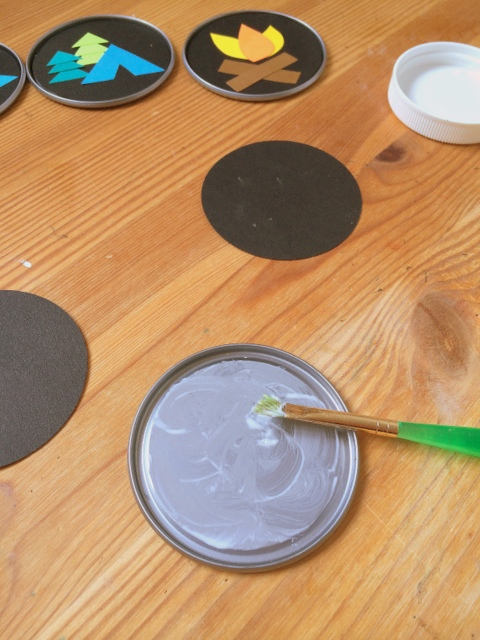 Using mod podge to glue the paper to the can lid - northstory.ca