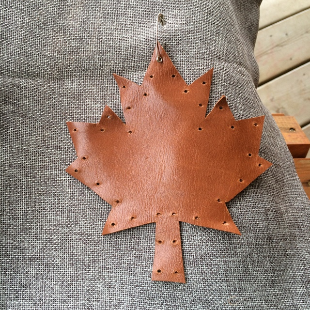 getting ready to hand stitch the leather leaf onto the pillow - northstory.ca