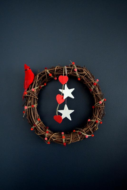 rustic-wreath-featuring-a-cardinal-felt-hearts-and-pom-pom-twine-garland