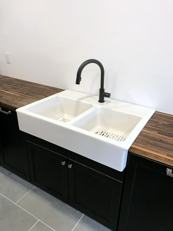 IKEA DOMSJO kitchen sink in a butcher block countertop with a black faucet